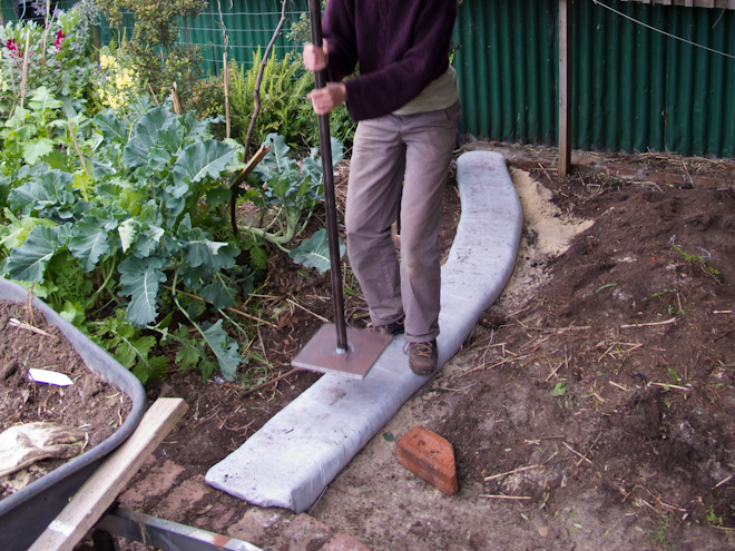 Tamping down the first earth bag for our super adobe garden bed in preparation for the Flemington Permablitz